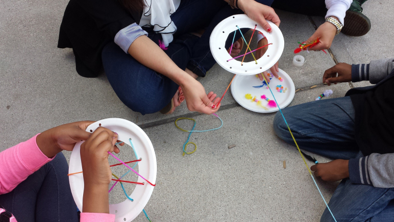 Pictured above students make dream catchers using paper plates, colored yarn, beads and feathers.