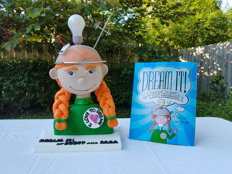 "3D cake sculpture of the main character in the ""Dream It! Playbook"" and the authors Sara E. Williams and Scott Stoll"