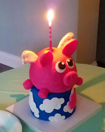A colorful, when-pigs-fly birthday cake with a candle.