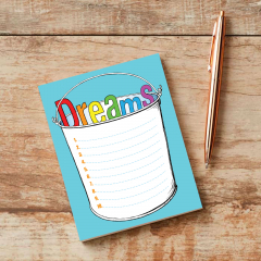 "A bucket with the word ""Dreams"" inside pictured here on a wooden table with a copper pen."