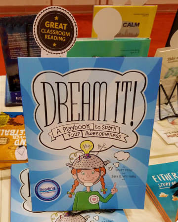 """Dream It!"" on the table at the American Psychological Association annual conference with a ""Reading Is Fundamental"" sticker and a ""Great Classroom Reading"" bookmark."