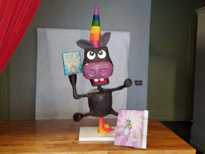 A cake that is a donkey dressed up as a unicorn holding a book that is another cake made out of Rice Krispie treats.