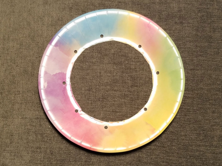 A colorful paper plate with the center cut out and 8 holes punched.