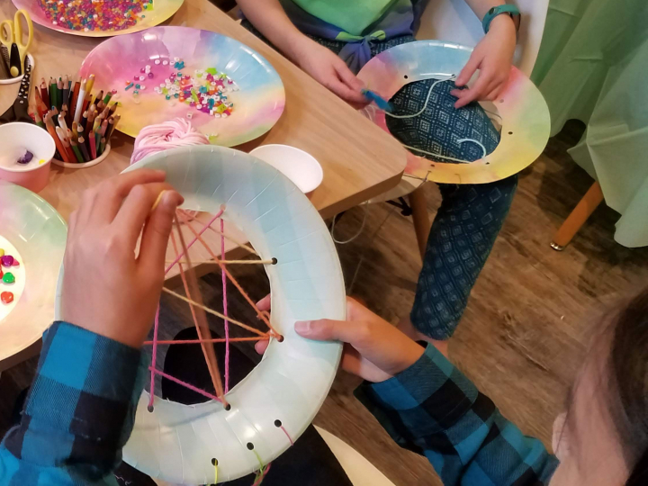 Dreamcatcher workstation and girls weaving a web with colorful yarn.