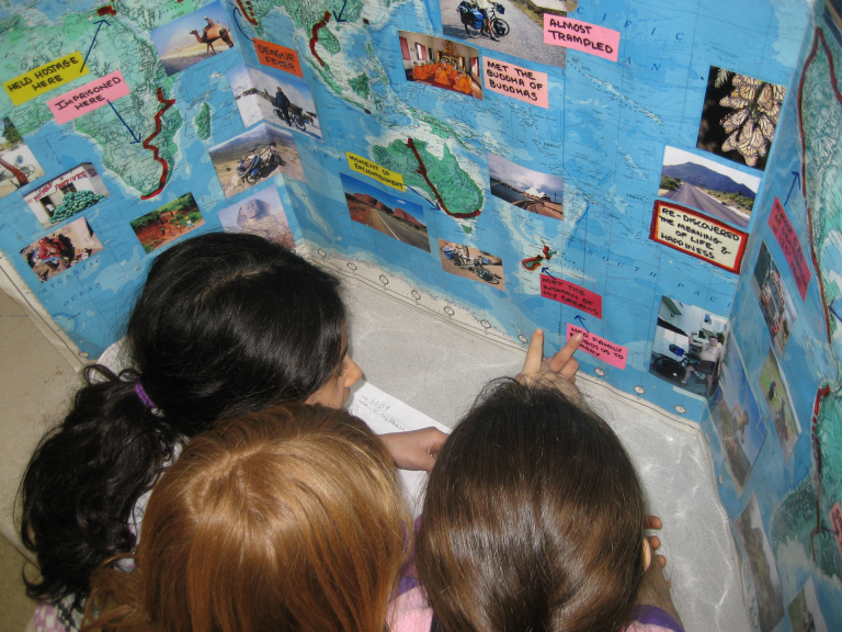 Elementary students looking the map of Scotts adventures