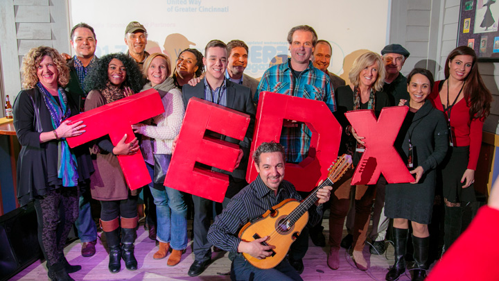 TEDx Happy Hour Group stands in the spotlight on stage