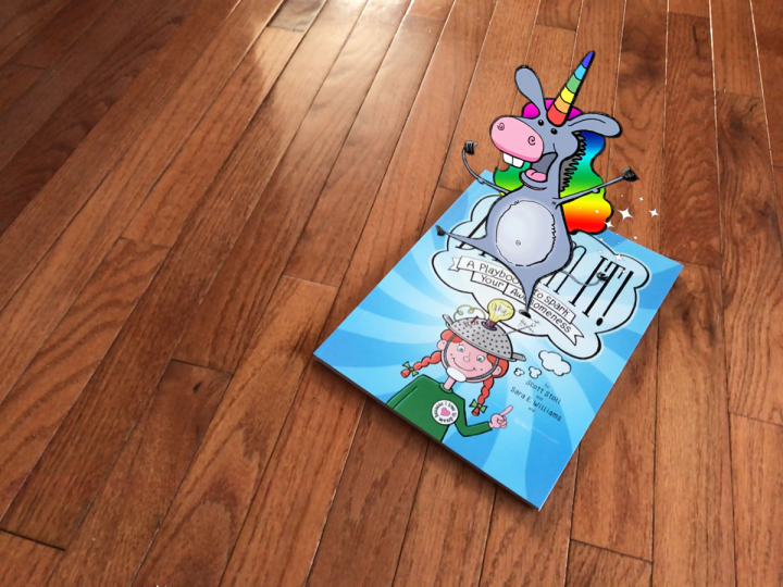 """The Donkeycorn standing on top of the book, """"Dream It!"""""""