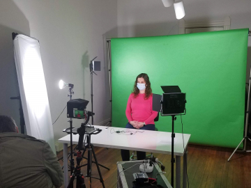 KMNH News. Sara sits in front of the green screen and cameras.