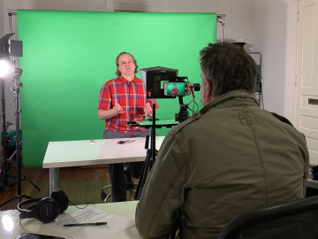 KMNH News. Scott sits in front of the green screen and cameras.